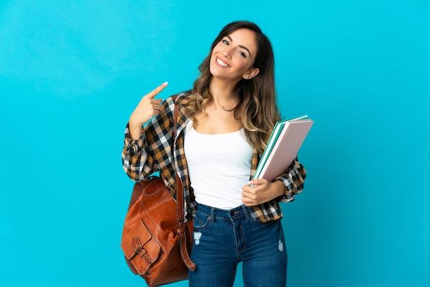Jovem estudante isolada em uma parede azul fazendo um gesto de polegar para cima