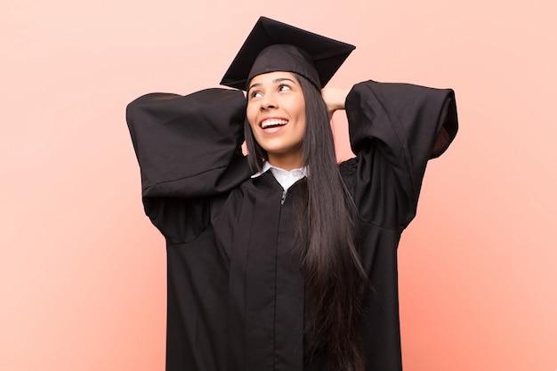 Jovem estudante latina sorrindo e se sentindo relaxado, satisfeito e despreocupado, rindo positivamente e relaxando
