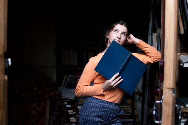 Jovem estudante lê um livro na biblioteca antiga, uma mulher está procurando informações nos arquivos