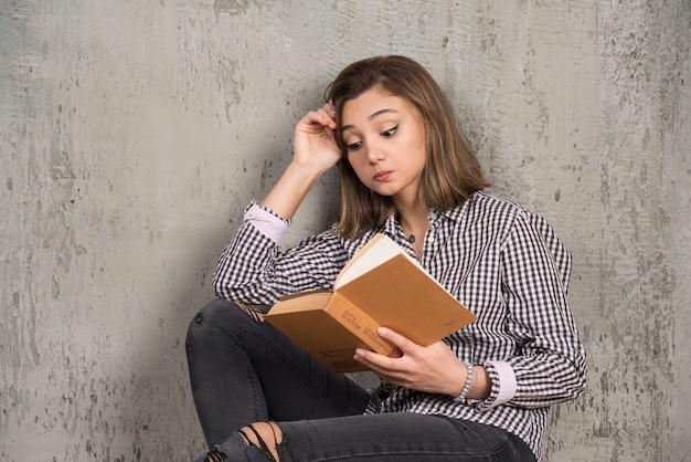 Jovem estudante lendo livro com cuidado sobre a parede de pedra