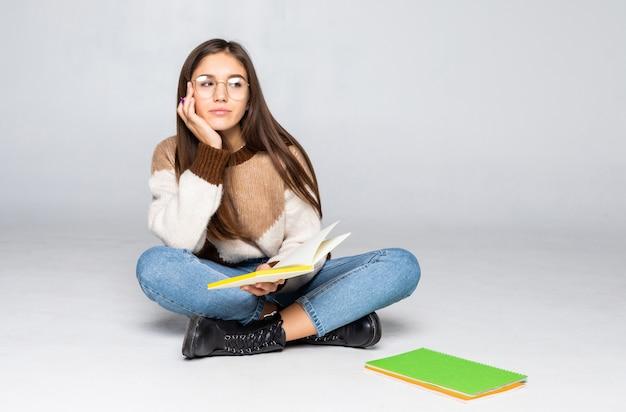 Jovem estudante linda sentada com livro, lendo, aprendendo. isolado na parede branca