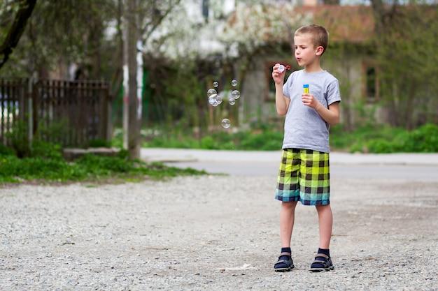 Jovem estudante loira bonita em roupas casuais com expressão séria engraçada sopra bulbos de sabão transparente em pé ao ar livre num dia quente de verão. conceito de infância feliz descuidado.