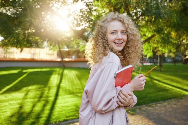 Jovem estudante loira caminha pelo parque, com um caderno vermelho e um lápis nas mãos