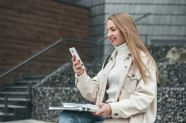 Jovem estudante loira caucasiana faz uma videochamada em um telefone celular e sorri enquanto está sentada em um banco perto de um prédio da faculdade