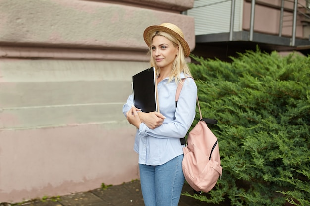 Jovem estudante loira em um chapéu de palha e uma mochila rosa frente da universidade