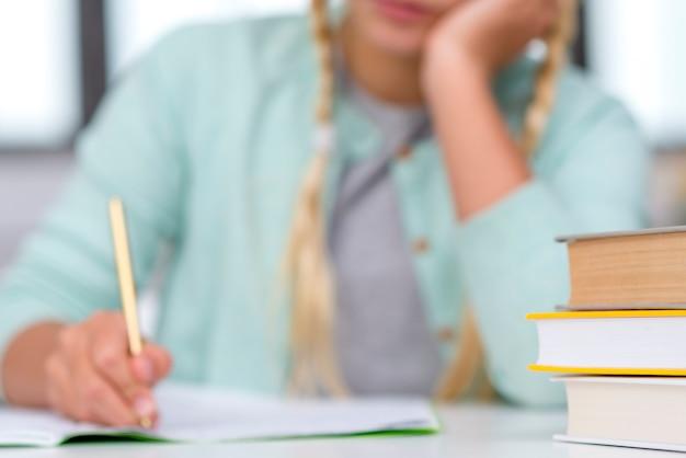 Jovem estudante loira escrevendo efeito turva