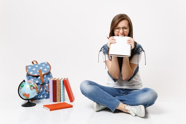 Jovem estudante louca e curiosa de óculos segurando um lápis roendo um caderno cortante, sentada perto da mochila globo, livros escolares isolados