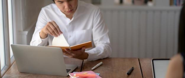Jovem estudante masculino, preparando-se para o exame na biblioteca