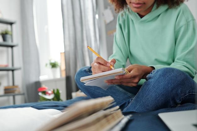 Jovem estudante mestiça em trajes casuais, sentada na cama em frente a um livro aberto e fazendo anotações no caderno enquanto se prepara para o exame