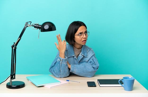 Jovem estudante mestiça estudando sobre uma mesa com problemas para fazer gestos suicidas