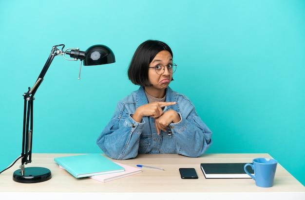 Jovem estudante mestiça estudando sobre uma mesa fazendo o gesto de se atrasar