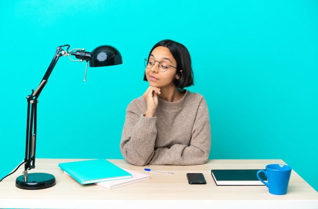 Jovem estudante mestiça estudando sobre uma mesa, tendo dúvidas enquanto olha de lado