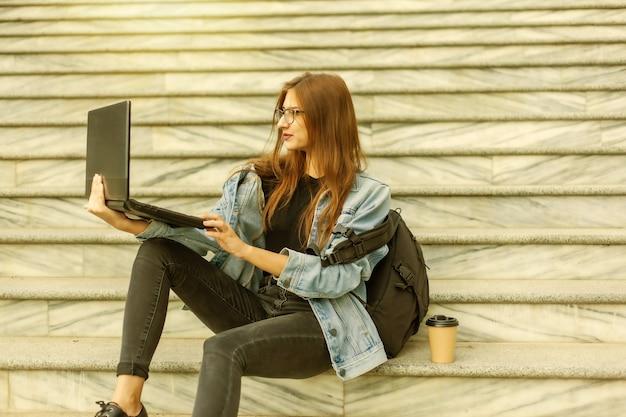 Jovem estudante moderna de jaqueta jeans e óculos, sentado na escada com o laptop. assistindo video. ensino à distância. conceito moderno da juventude.