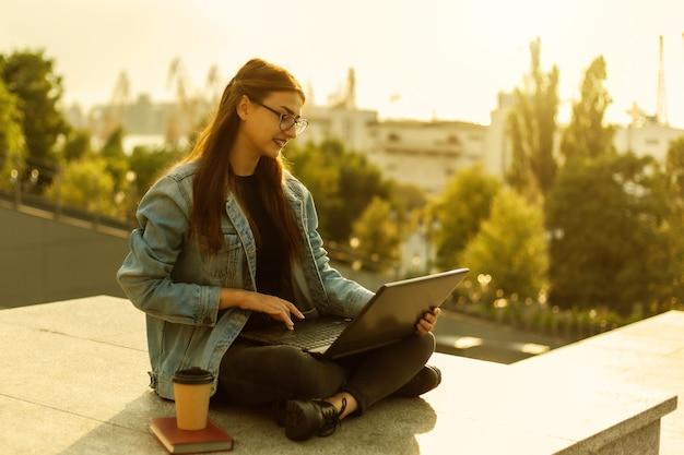 Jovem estudante moderna em uma jaqueta jeans, sentada e usa o laptop ao ar livre. ensino à distância. conceito moderno da juventude.