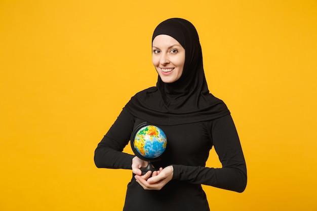 Jovem estudante muçulmana árabe em roupas pretas de hijab segura nas mãos, globo do mundo terrestre isolado no retrato de parede amarela. conceito de estilo de vida religioso de pessoas.