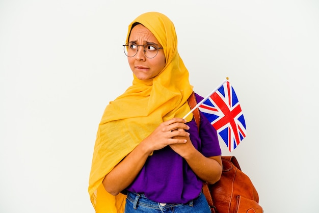 Jovem estudante muçulmana isolada na parede branca confusa, sente-se duvidosa e insegura