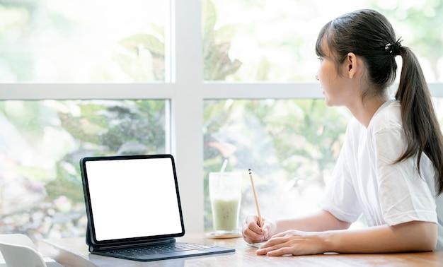 Jovem estudante muito asiática usando computador tablet e escrevendo no caderno enquanto siiting à mesa na sala de estar em casa, conceito de leraning online. tela em branco para design gráfico.