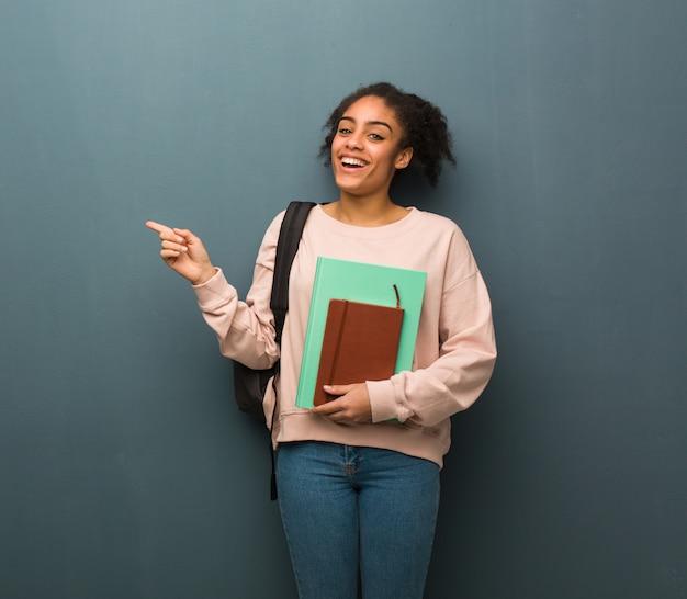 Jovem estudante mulher negra, apontando para o lado com o dedo, ela está segurando livros