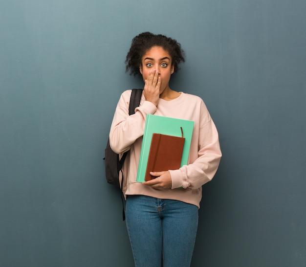 Jovem estudante mulher negra muito assustada e com medo escondido. ela está segurando livros.