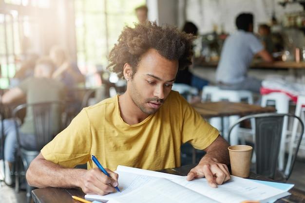 Jovem estudante negro, vestido casualmente, com barba e cabelos cacheados, tendo um olhar concentrado enquanto lê informações no livro e fazendo anotações no caderno, preparando-se para a aula na faculdade