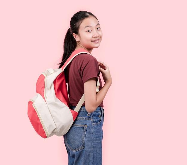 Jovem estudante no colégio sorrindo para a parede rosa da câmera