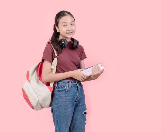 Jovem estudante no colégio sorrindo para a parede rosa da câmera Foto Premium