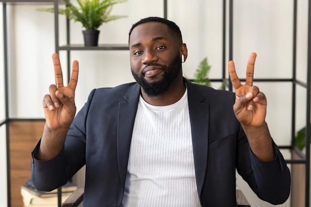 Jovem estudante ou empresário afro-americano participa de negociações virtuais à distância por teleconferência em casa. conceito de videochamada