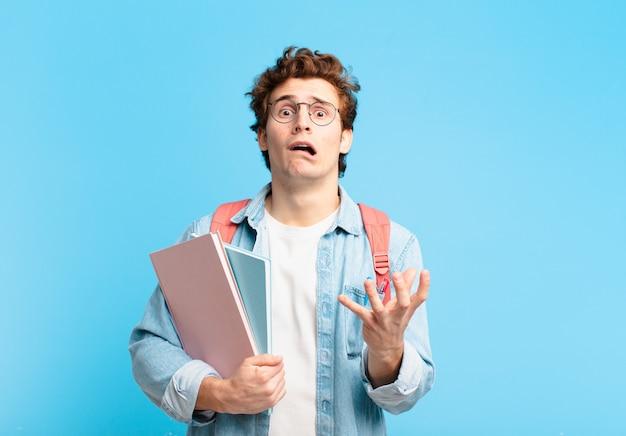 Jovem estudante parecendo desesperado e frustrado, estressado, infeliz e irritado, gritando e gritando