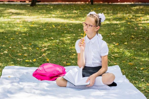 Jovem estudante pondera lição de casa enquanto está sentada em um cobertor em um parque ensolarado de outono. educação ao ar livre para crianças. conceito de volta às aulas