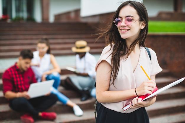 Jovem estudante posando com bloco de notas