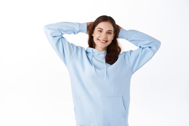 Jovem estudante relaxada, tendo momentos de lazer, segurando as mãos atrás da cabeça como se estivesse deitada e descansando, sorrindo feliz na frente, em pé contra uma parede branca