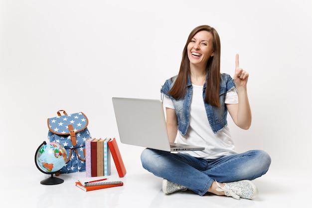 Jovem estudante rindo segurando o computador laptop pc apontando o dedo indicador sentada perto do globo, mochila, livros escolares isolados