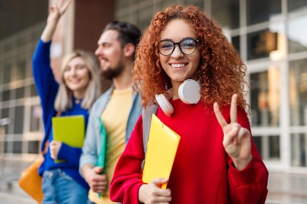 Jovem estudante ruiva mostrando gesto de vitória com amigos