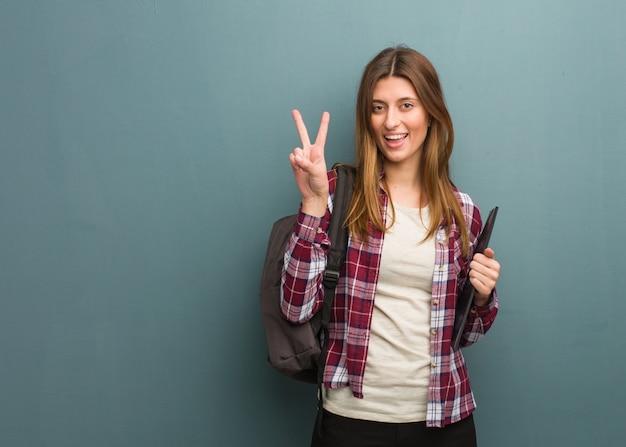 Jovem estudante russa mulher divertida e feliz fazendo um gesto de vitória