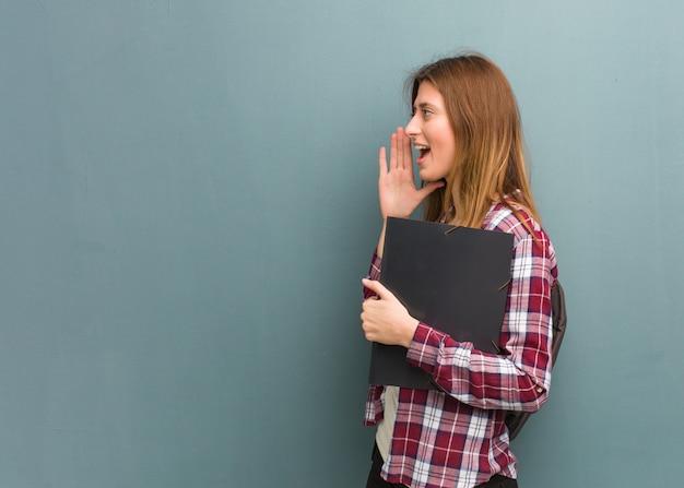 Jovem estudante russo mulher sussurrando fofoca tom