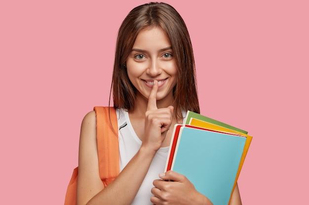 Jovem estudante satisfeita posando contra a parede rosa