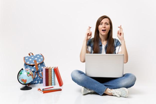 Jovem estudante segurando um laptop esperando por um momento especial, mantendo os dedos cruzados perto da mochila de livros escolares do globo isolados