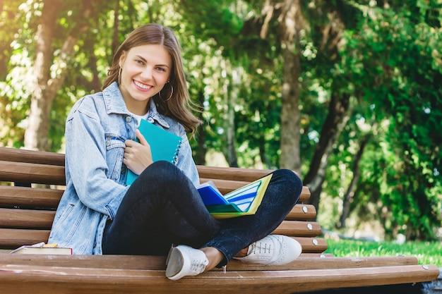 Jovem estudante senta-se em um banco no parque e detém livros, cadernos e pastas. menina ensina lições no parque.