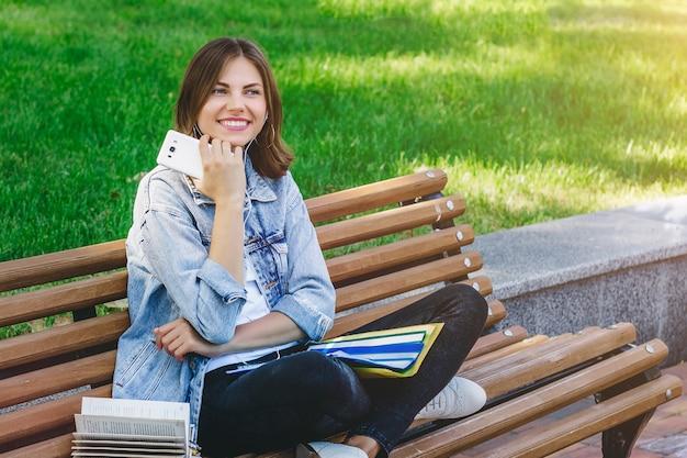 Jovem estudante senta-se em um banco no parque e detém livros, cadernos e telefone móvel. menina ensina lições no parque.