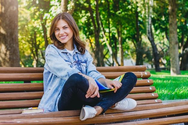 Jovem estudante senta-se em um banco no parque e detém livros, cadernos.