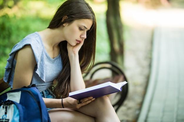 Jovem estudante sentada no banco lendo um livro no parque