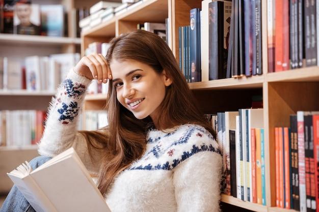 Jovem estudante sentada no chão da biblioteca lendo um livro na faculdade