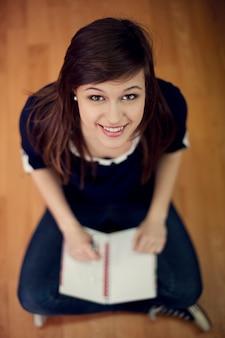 Jovem estudante sentado no chão