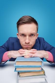 Jovem estudante sério segurando o queixo sobre as mãos, segurando uma pilha de livros, enquanto está sentado perto da mesa
