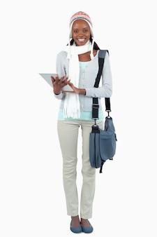 Jovem estudante sorridente com lenço, chapéu e touchpad