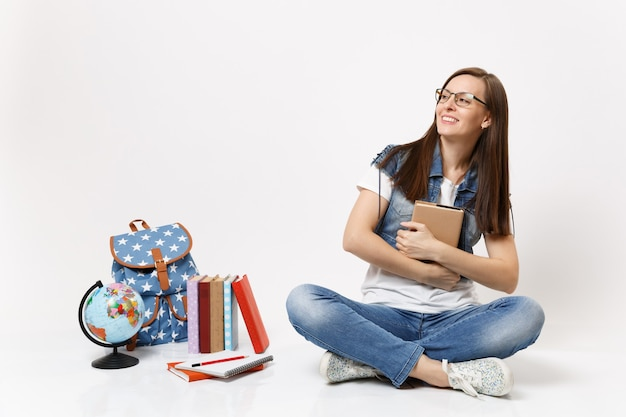 Jovem estudante sorridente com óculos jeans segurando um livro olhando para o lado, sentada perto do globo, mochila, livros escolares isolados