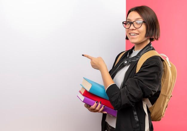 Jovem estudante sorridente de óculos e bolsa com as costas segurando livros em frente a uma parede branca, apontando para eles isolados na parede rosa