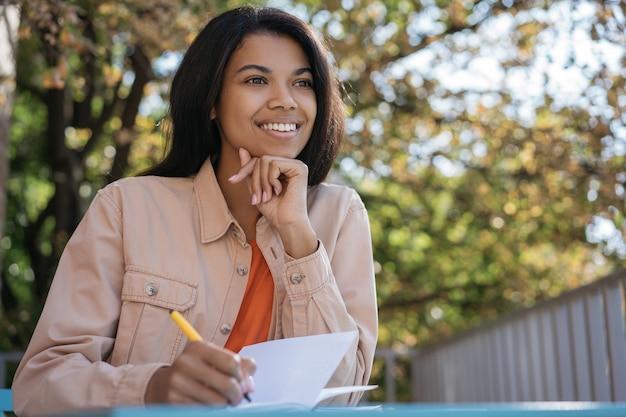 Jovem estudante sorridente, estudando, aprendendo línguas, escrevendo, o conceito de educação