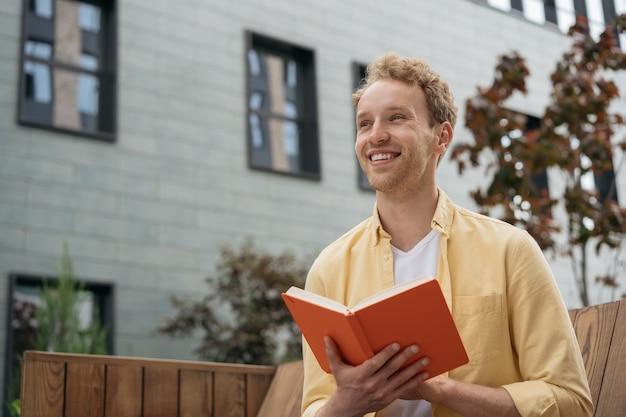 Jovem estudante sorridente, estudando, lendo um livro, sentado no banco do campus da universidade