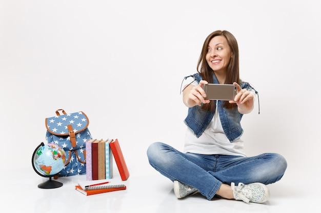Jovem estudante sorridente fazendo selfie tirada no celular, olhando para o lado, sentada perto do globo, mochila, livros escolares isolados